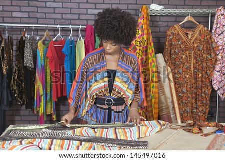 African American female designer measuring cloth at design studio - stock photo