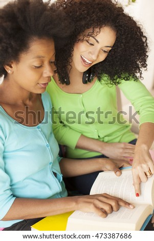 African american female friends reading book outdoors