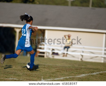African American girl chases the soccer ball - stock photo