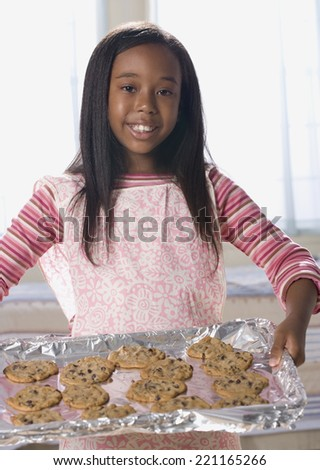 African American girl holding tray of cookies - stock photo