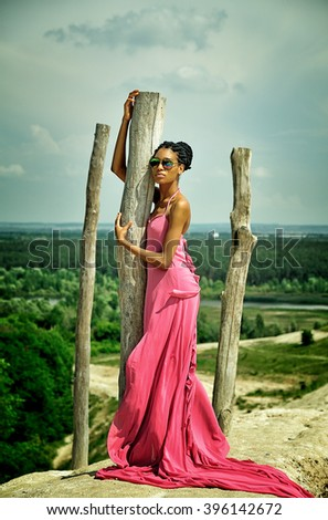 African American girl in a pink dress, wearing sunglasses in summer is high on a hill against the sky and beautiful scenery and is behind the tree. Vertical view - stock photo
