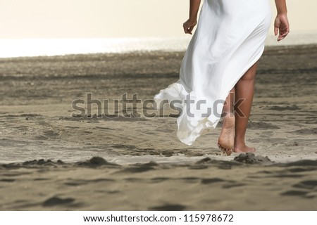 African American girl is walking on the beach close up on feet - stock photo