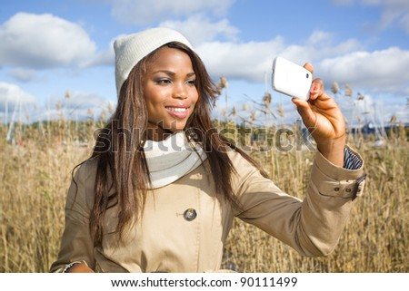 African american girl taking pictures with cellphone