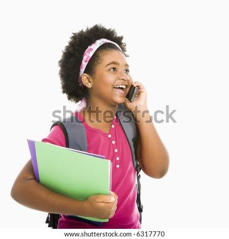 African American girl with books and wearing backpack talking on cell phone. - stock photo
