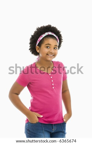 African American girl with hands in pockets wearing headband smiling at viewer. - stock photo