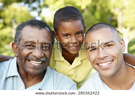 African American Grandfather, Father And Son Relaxing In Park - stock photo