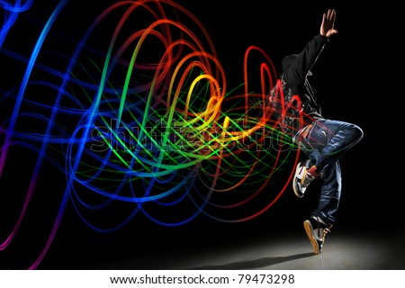 African American hip hip dancer with waves of light painting over dark  background - stock photo