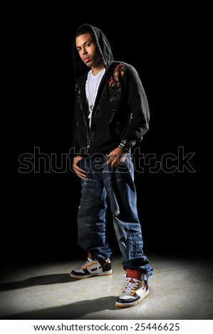 African American hip hop dancer standing over a dark background - stock photo