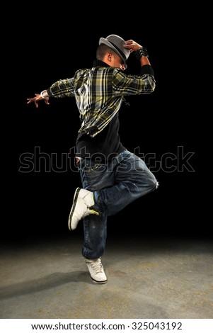 African American hop hop dancer performing over dark background - stock photo