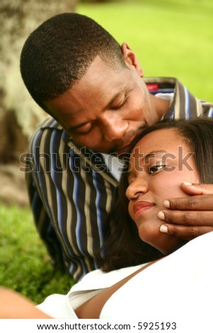 african american husband kissing his wife while she is reading a book in a park - stock photo