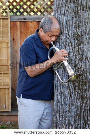 African american jazz musician posing with his flugelhorn outside. - stock photo