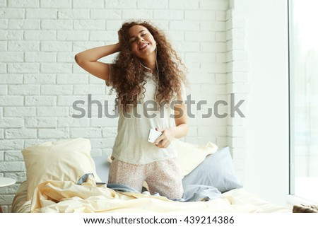 African American listening to music in earphones on bed - stock photo
