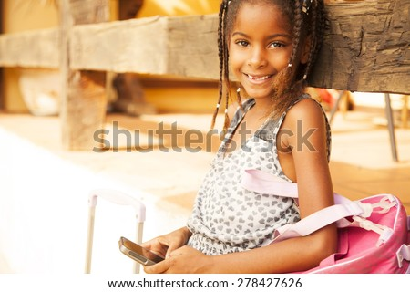African american little girl with mobile phone and backpack