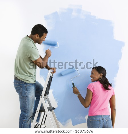 African American male and female couple painting wall blue and smiling at each other. - stock photo