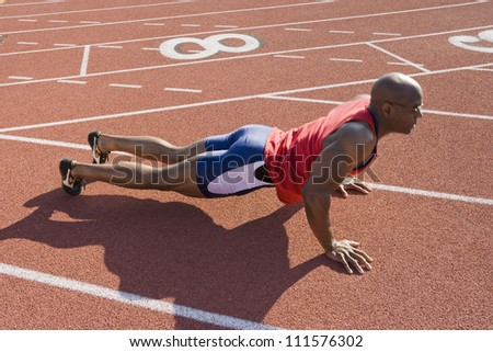 African American male athlete makes push-ups on a racetrack