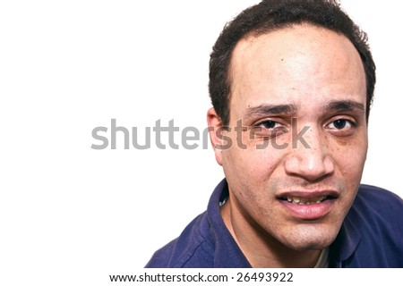 african american male dressed in blue shirt againt white background with a grimace on face looking upset