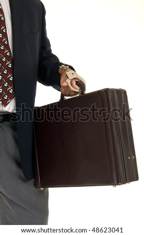 African American male hand cuffed to a briefcase. - stock photo