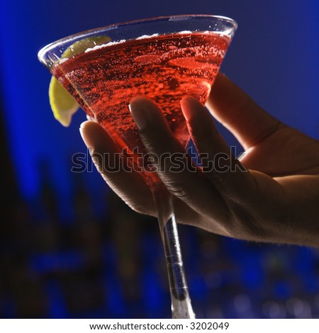 African American male hand holding martini in bar against glowing blue background.