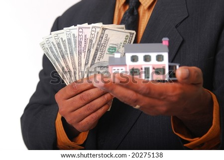 African-American male hands holding a miniature house and American currency. Shallow DOF with focus on money.