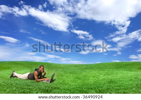 African American Male Outdoors on a Laptop on Grass - stock photo