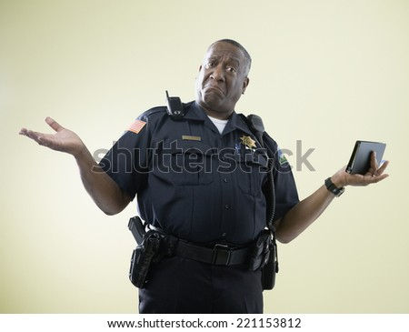 African American male police officer shrugging shoulders - stock photo