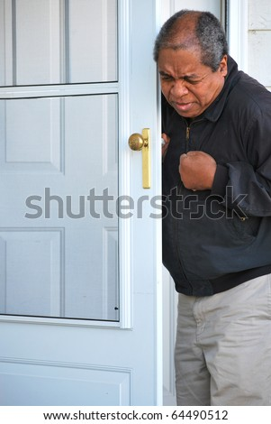 African american male starting to have chest pains just as he leaves his house. - stock photo