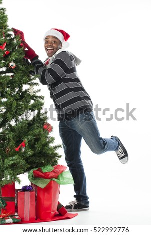 African American male with great smile decorating a tree in studio isolated on white