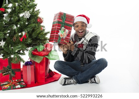 African American male with great smile opening gifts by the christmas tree in studio isolated on white