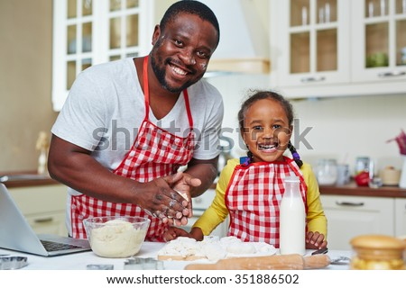 African-American man and little girl cooking homemade pastry together - stock photo