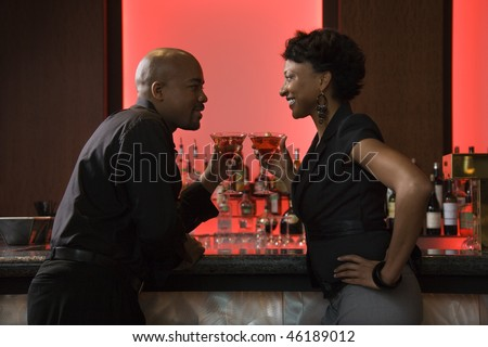 African-American man and woman face each other at a bar while enjoying martinis. Horizontal shot. - stock photo