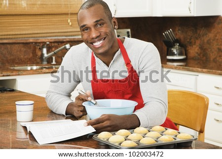 African American man baking with cookbook - stock photo