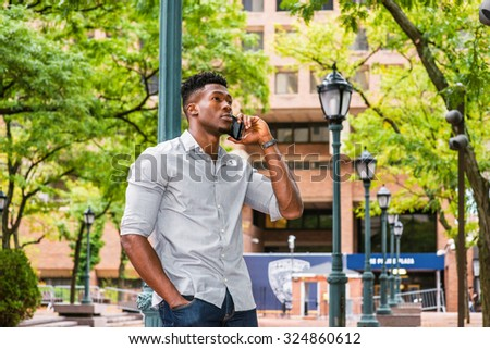 African American Man calling outside. Wearing gray shirt, rolling over sleeves, a black guy standing against light pole on street in New York, looking up, seriously listening to cell phone.  - stock photo