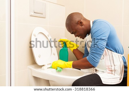 african american man cleaning toilet at home - stock photo