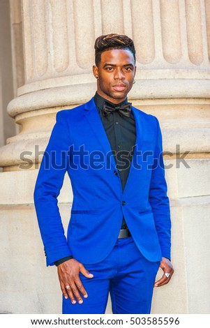 African American Man Fashion in New York. Dressing formally in blue suit, black shirt, bow tie, wearing ear ring, finger ring, black man with afro hairstyle stands by column on street, looking forward