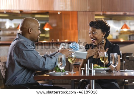 African-American man giving a surprised woman a gift-wrapped present at a restaurant. Horizontal shot. - stock photo