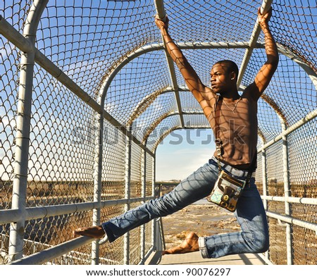 African American man hanging from a chain link fence.