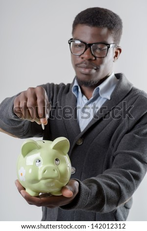 African-American man holding a piggy bank - stock photo