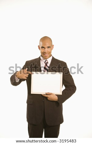 African American man holding and pointing to blank sign standing against white background. - stock photo