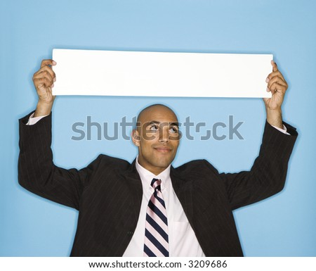 African American man holding blank sign against blue background. - stock photo