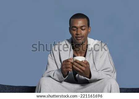 African American man holding coffee mug - stock photo