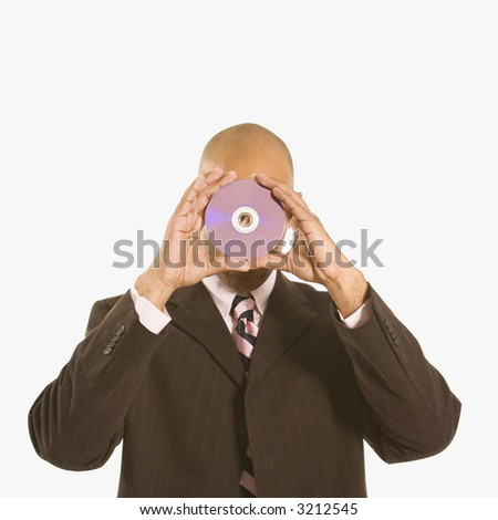 African American man holding compact disc over his face. - stock photo