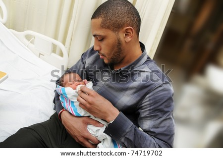 African American Man Holding Feeding Healthy Newborn Infant Baby Child in Hospital Room - stock photo