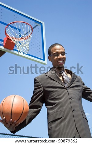 African American man in a business suit posing with a basketball.  He could be a coach player recruiter scout or trainer. - stock photo