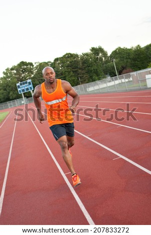 African American man in his 30s running at a sports track outdoors. - stock photo