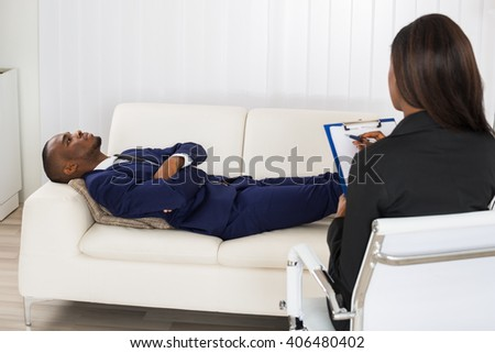 African American Man Laying On Couch In Front Of Psychiatrist With Clipboard - stock photo