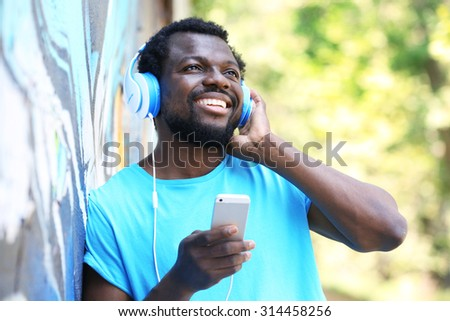African American man listening music with headphones near graffiti wall outdoors - stock photo