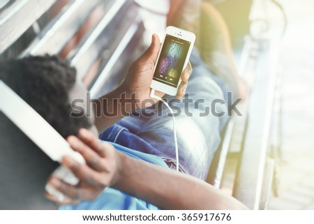African American man listening music with headphones on bench in park - stock photo
