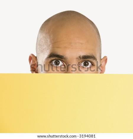 African American man peeking over blank yellow sign. - stock photo