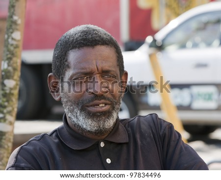 African American man sitting and relaxing outdoors during the daytime. - stock photo