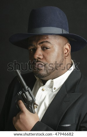 African American man wearing a hat and with a gun over a gray background